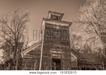 old abandoned schoolhouse in rural Nebraska overgrown by trees and weeds, sepia toned image