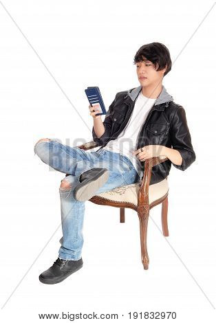 A handsome Asian man in a black leather jacket talking on his cell phone sitting in an old armchair isolated for white background.