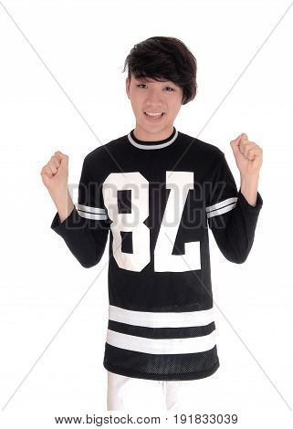 A handsome young Asian teenager standing in a black t-shirt with his fists up celebrating victory isolated for white background.
