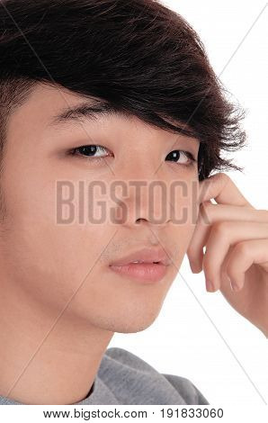 A closeup portrait image of a young Asian man with his hand on his face serious isolated for white background.