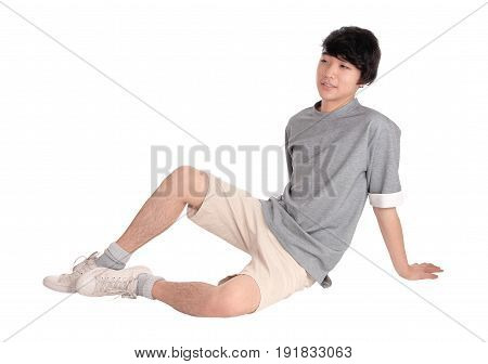 A handsome pretty young Asian teenager sitting in shorts on the floor smiling isolated for white background.