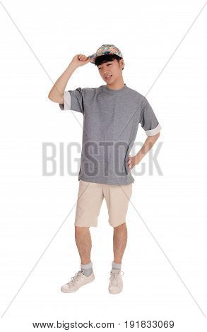 A young Asian teenager standing in shorts an a gray t-shirt with his hand on his cap isolated for white background.