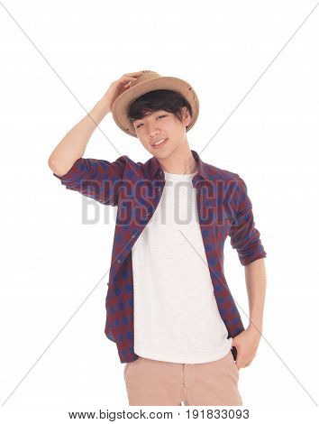 A happy Asian teenager standing in an checkered shirt holding his hand on his hat isolated for white background.