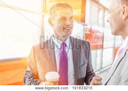 Middle aged businessman talking with male colleague in railroad station