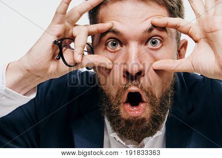 Business man widened his eyes with his hands, businessman holds glasses, businessman on a light background portrait.