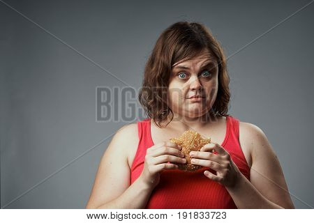 Hungry woman eating a hamburger woman with a hamburger on a gray background.
