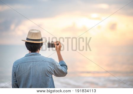 Young Asian man traveler and photographer with jean shirt and hat taking photos of beautiful sunset at tropical beach island background for summer holiday and vacation travel concepts