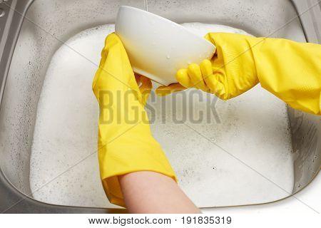 Hands In Gloves Washing White Bowl Under Running Tap Water
