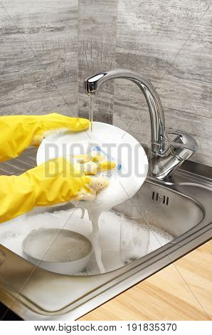 Hands In Gloves Washing White Plate With Blue Rag