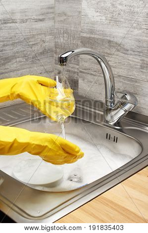 Hands In Gloves Washing Wine Glass Under Running Tap Water