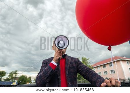 Man speaking over a megaphone as he makes a public address, participates in a protest or organises a rally or promotion