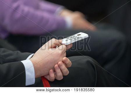 Businessman in  holds control panel voting. Business conference