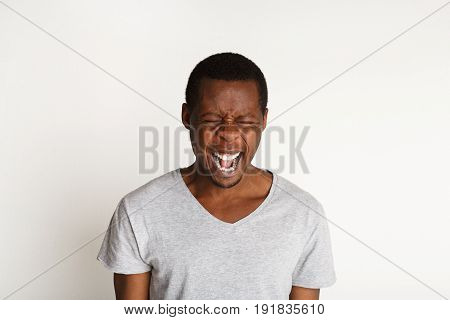 Black man cry out in despair and shock. Expressing strong emotions, anger, on white background, studio shot