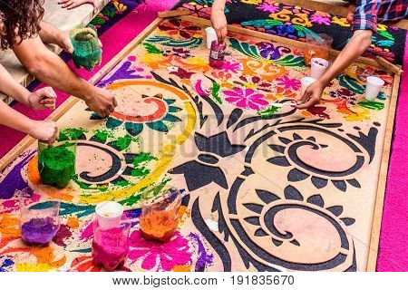 Antigua, Guatemala - April 13 2017: Making dyed sawdust Holy Week carpet for procession in colonial town with most famous Holy Week celebrations in Latin America