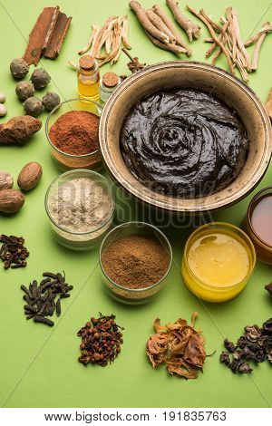 Flat lay of a bowl of Chyawanprash or chyavanprash and all its ingredients on a green background.