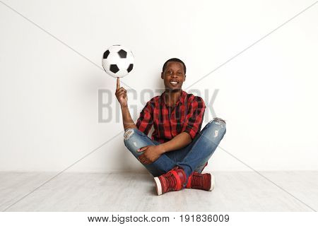 Happy african-american man spinning soccer ball on his finger sitting with crossed legs on a white background