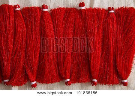 Red tassels line close up, handicraft. Art, creativity, hobby, home workshop concept