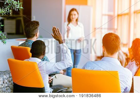 African american Business people Raising there Hand Up at a Conference to answer a question.