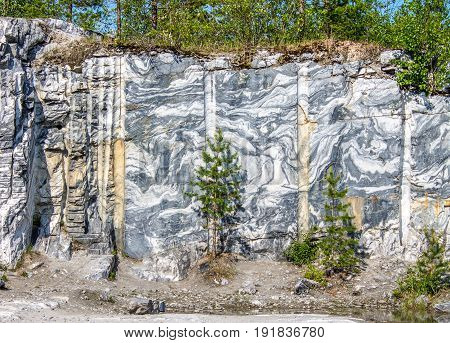 Marble quarry, marble rocks in the wild in the Republic of Karelia, Russia. The natural stone. Ancient Marble quarry, marble rocks in the wild. Slices of marble mountain. Tourism and travel.