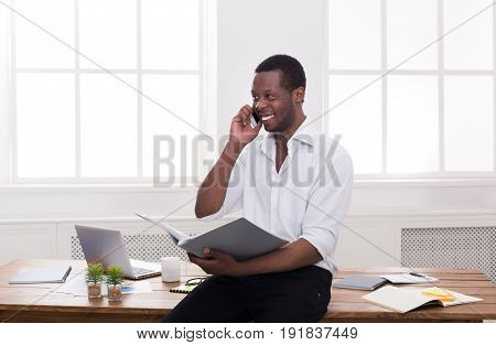 Black businessman with papers and mobile. Young man discussing documents on cellphone in modern office, copy space