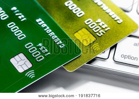 work place with business credit cards on keyboard for payment on white office desk background close up