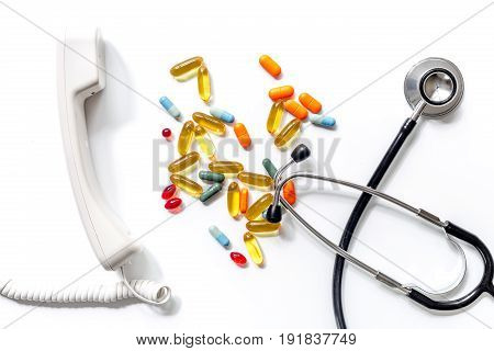 Medical things with notebook on white background top view composition with phonendoscope and drugs call doctor.