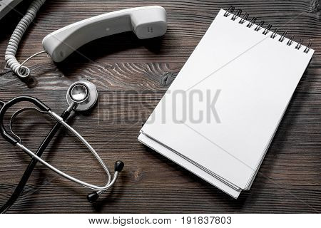 phone handset, phonendoscope and notebook on dark wooden desk top view call doctor.