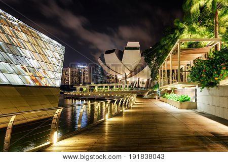 Singapore - February 16 2017: Amazing night view of wooden walkway along Marina Bay in Singapore.