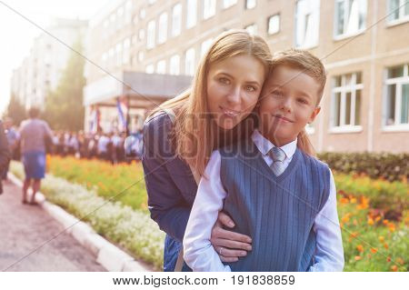 The first time in first class: happy schoolboy with his mother going to the school in first time
