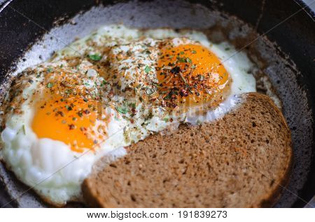 Fried eggs with bread in a frying pan and sprinkled with seasoning