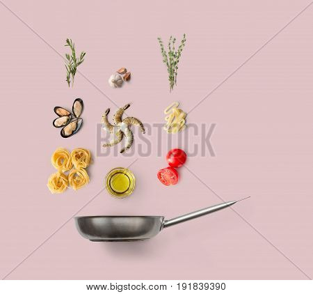 Cooking seafood pasta, ingredients isolated on pink background. Frutti di mare with fettuccine spaghetti. Mussels, prawn, shrimp, calamari rings and other ingredients over frying pan
