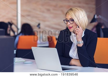 Good business talk. Cheerful young beautiful woman in glasses talking on mobile phone and using laptop with smile while sitting at her working place