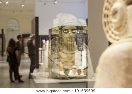 Madrid Spain - February 24 2017: Lady of Elche reflections. People observing the most important piece of Iberian art at National Archeological Museum of Madrid