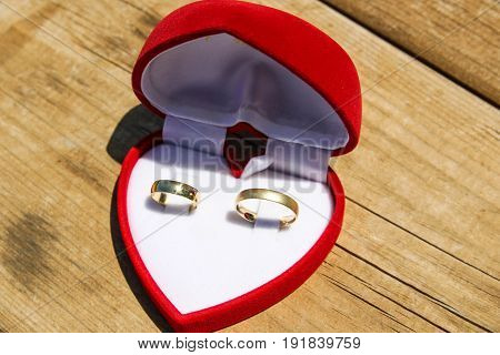 A Velvet Red Box With A Pair Of Gold Wedding Rings