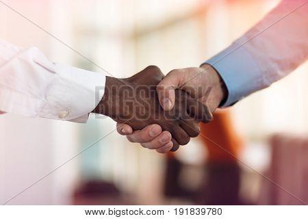 Handshake between african and a caucasian man.