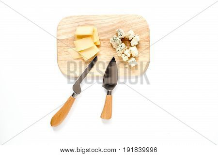 Aperitive parmesan cheese and cheese with blue mould on a cutting board on white background.