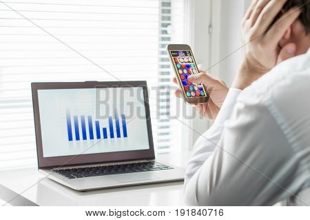 Lazy office worker playing mobile game with smartphone during work hours. Avoiding his job and leaning head against hand. Bored employee. Useless and unproductive man doing nothing and forget his job.