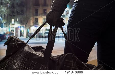 Terrorist standing and holding black bomb bag in hand with leather gloves. Man planning a dangerous explosion in city center. Suicide bomber at night. Terrorism and security concept.