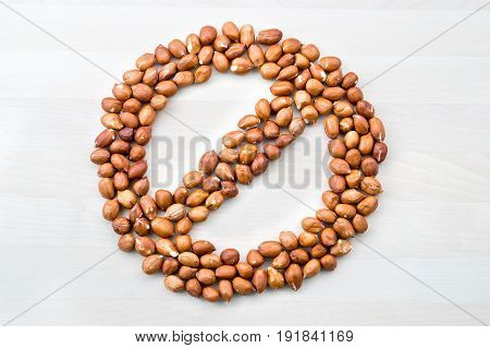 Peanut allergy. Stop, forbidden, prohibited and banned sign and symbol formed with nuts on white wooden table or board. No groundnuts for allergic person.