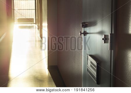 Unwanted or noisy neighbor living next door. Apartment building corridor with sunlight coming from window. One suspicious and dark shadowy flat entrance. Dangerous tenant.Dramatic color contrast. poster