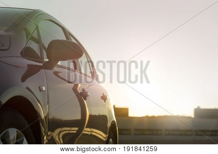 Summer time sunset or sunrise cruising in urban city. Car background or template with copy space. Modern vehicle driving in sun light, close view, side visible. Building silhouettes.