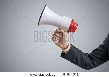Announcement concept. Hand holds megaphone on gray background.