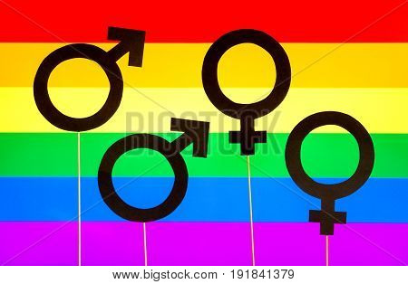 Homosexuality and gay pride banner. Gender symbols against LGBT rainbow flag. Homosexual and lesbian couple. Sexual minority concept. Four cardboard signs on wooden sticks and colorful background.