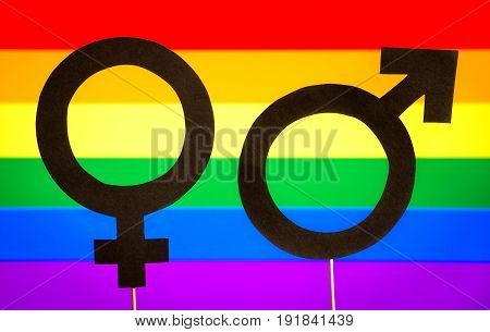 Gender symbols with LGBT rainbow flag background. Gay pride, homosexuality, and sexual minority concept. Man and woman support equality. Male and female cardboard signs on wooden sticks.