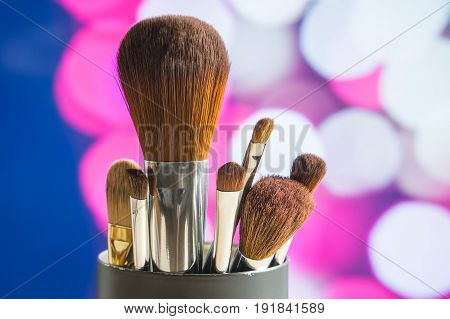 Close up of make up paint brushes with purple pink abstract bokeh background. Make up artist set with blurred city lights. Glamour and luxury layout. Banner or cover image for tutorials or services.