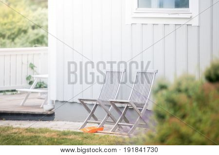 Garden chairs and white house. Green grass. Sweden Europe Scandinavia.