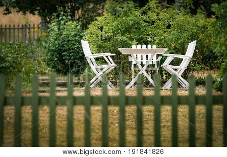 Garden chairs and table behind fence. Green grass and trees. Sweden Europe Scandinavia.