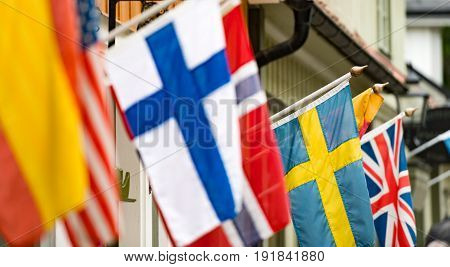 Many flags on wall of building in old town Sigtuna. Europe travel. Sweden Scandinavia.