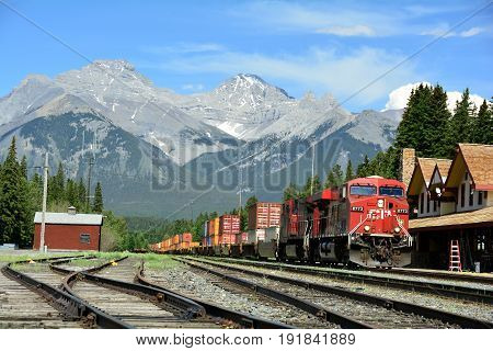 Banff National Park,Alberta,Canada,June 4th 2014.A cargo train passes through Banff train station on its way to the west coast to deliver its goods,leaving the mountain scenery in the distance.