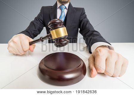 Young man in suit with gavel. Auction or justice concept.